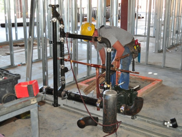 Hooper plumbing working on sanitary waste piping.