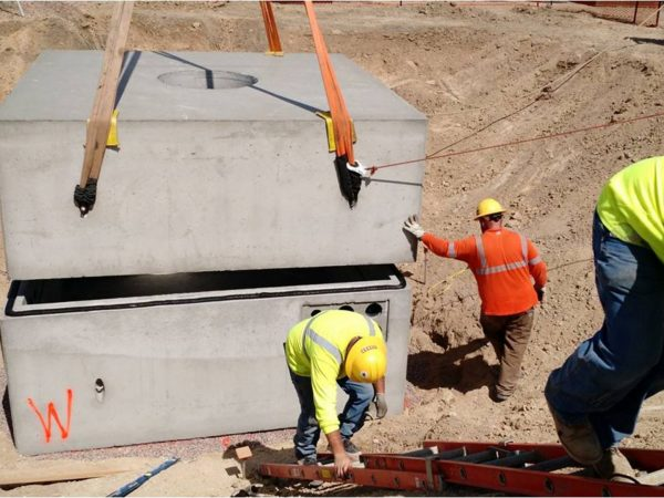 Crews set the new 2-stage below-grade vault to intercept underground power cable circuits.