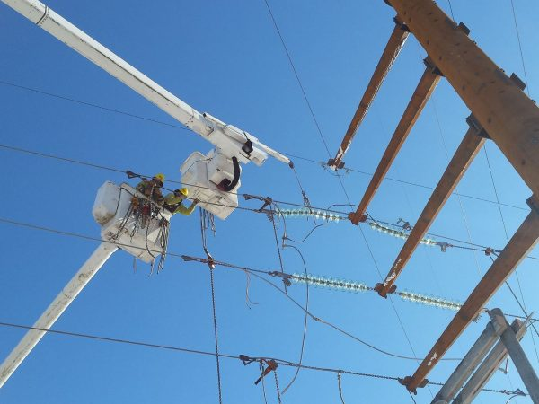 Crew adjusts tension on the wire in preparation to make up deadends.