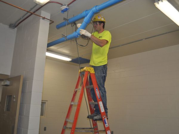 Installation of overhead vacuum piping.